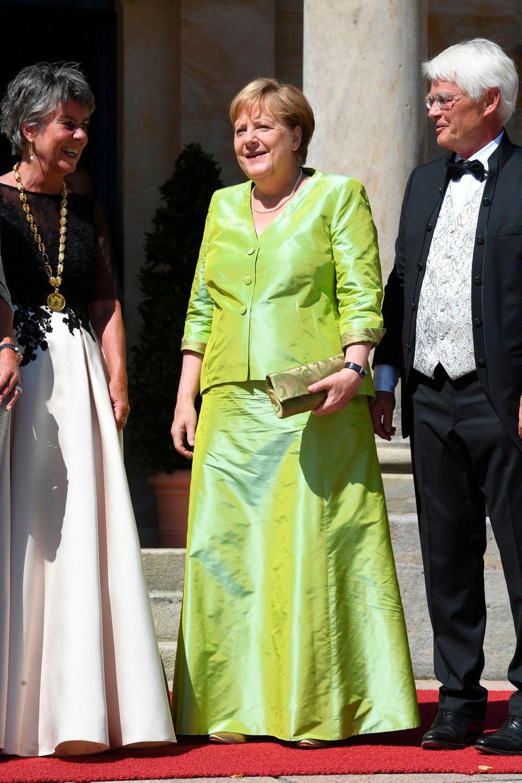 In einem glänzend-grünen Zweiteiler strahlt Angela Merkel mit der Sonne in Bayreuth um die Wette. Seit Jahren gehört sie zu den wichtigsten Gästen der Bayreuther Festpiele, die jährlich zu Ehren der letzten zehn Opern Richard Wagners auf dem Grünen Hügel stattfinden. Ob sie uns mit diesem Look klarmachen möchte, dass bei ihr nach den Zitteranfällen alles im Grünen ist?