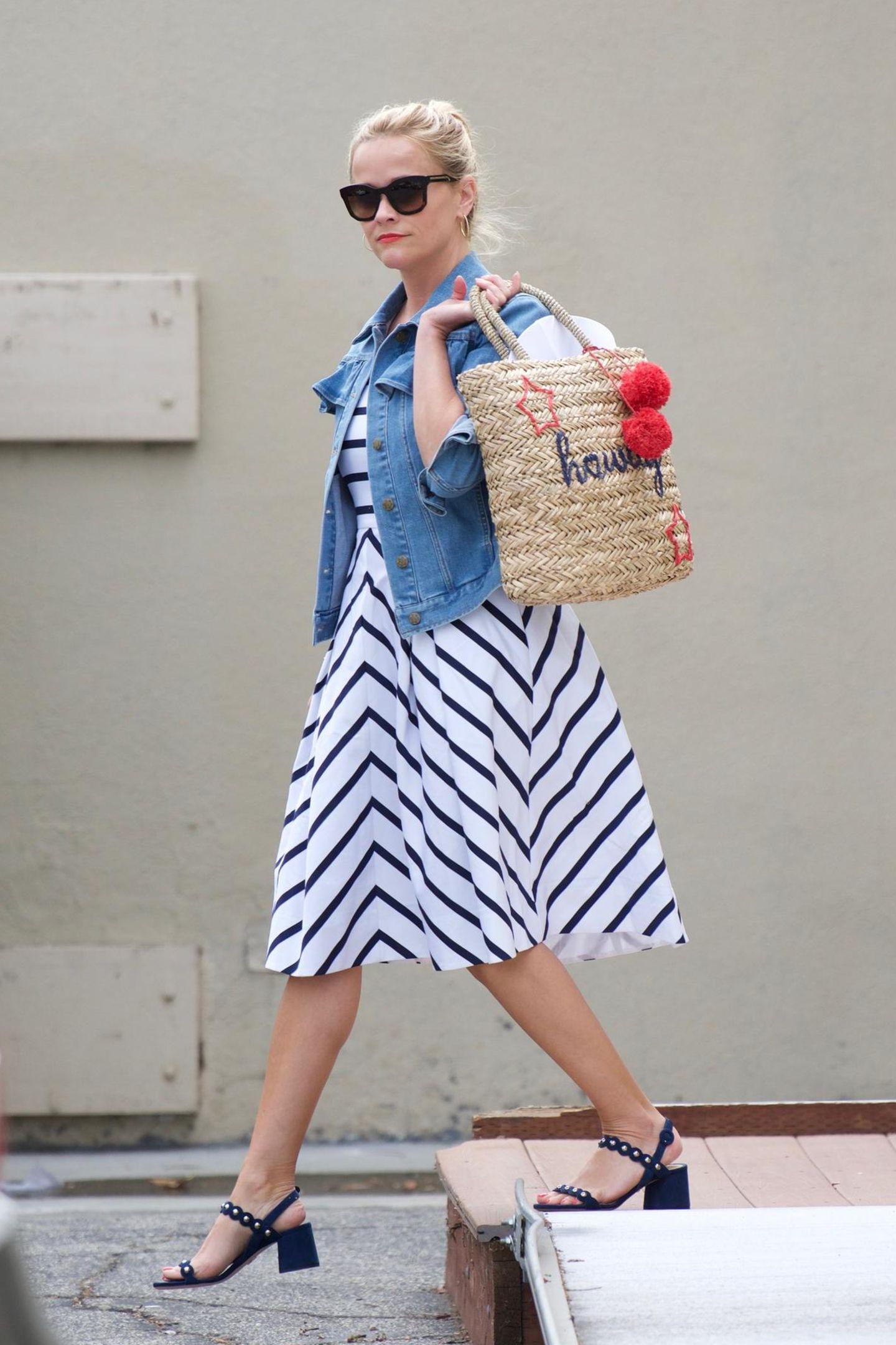 """Bei Reese Witherspoon schreit nicht nur die Strandtasche """"Howdy, Sommer"""". Ihr ganzer Look passt zur warmen Jahreszeit. Und sollte es im Schatten doch kühler sein, streift sie einfach ihre Jeansjacke über."""