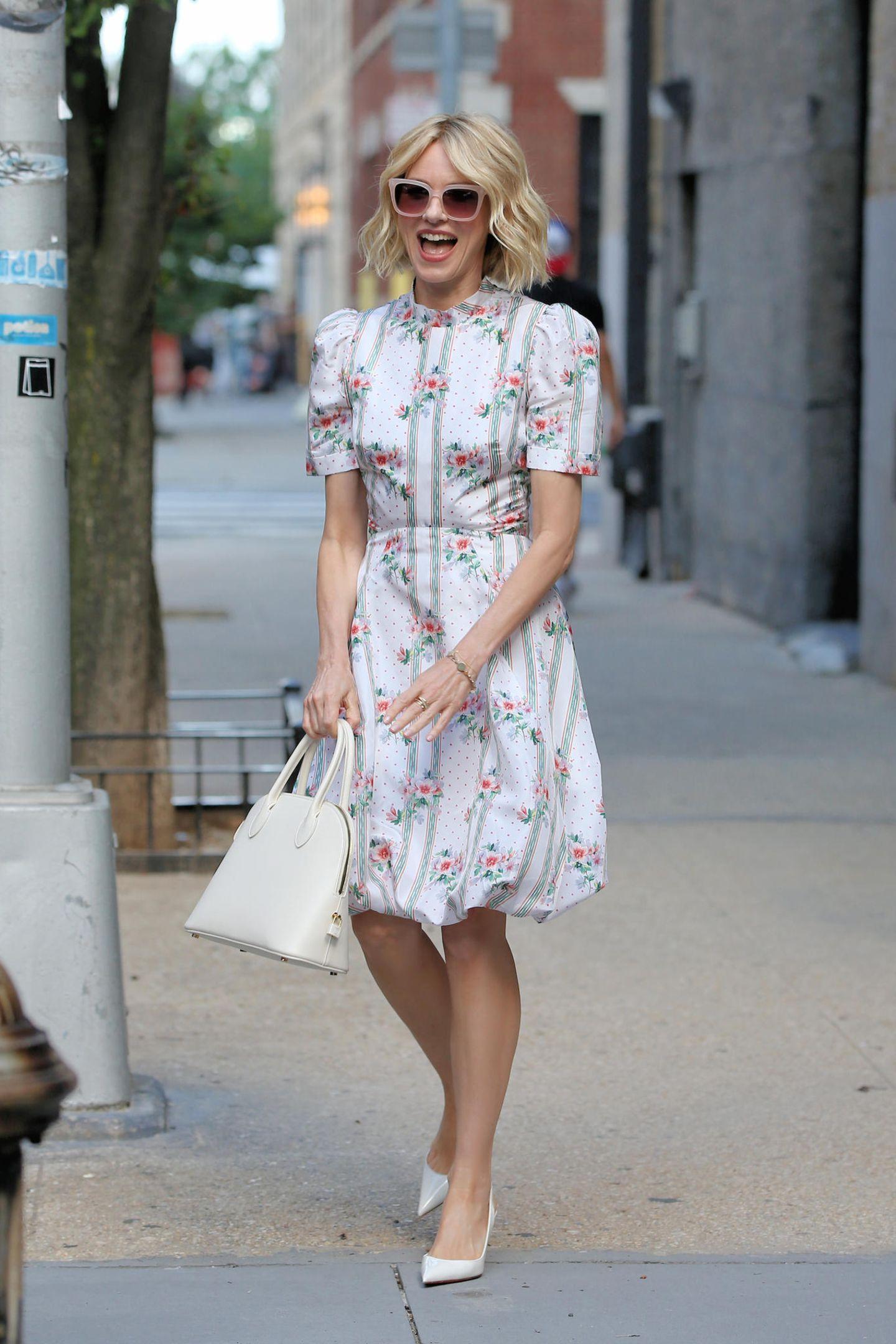Naomi Watts versprüht in einem romantischen Sommerkleid von Brock Collection extrem viel gute Laune. Zu dem It-Piece wählt sie weiße Pumps und eine weiße Handtasche - ideal, wie wir finden!