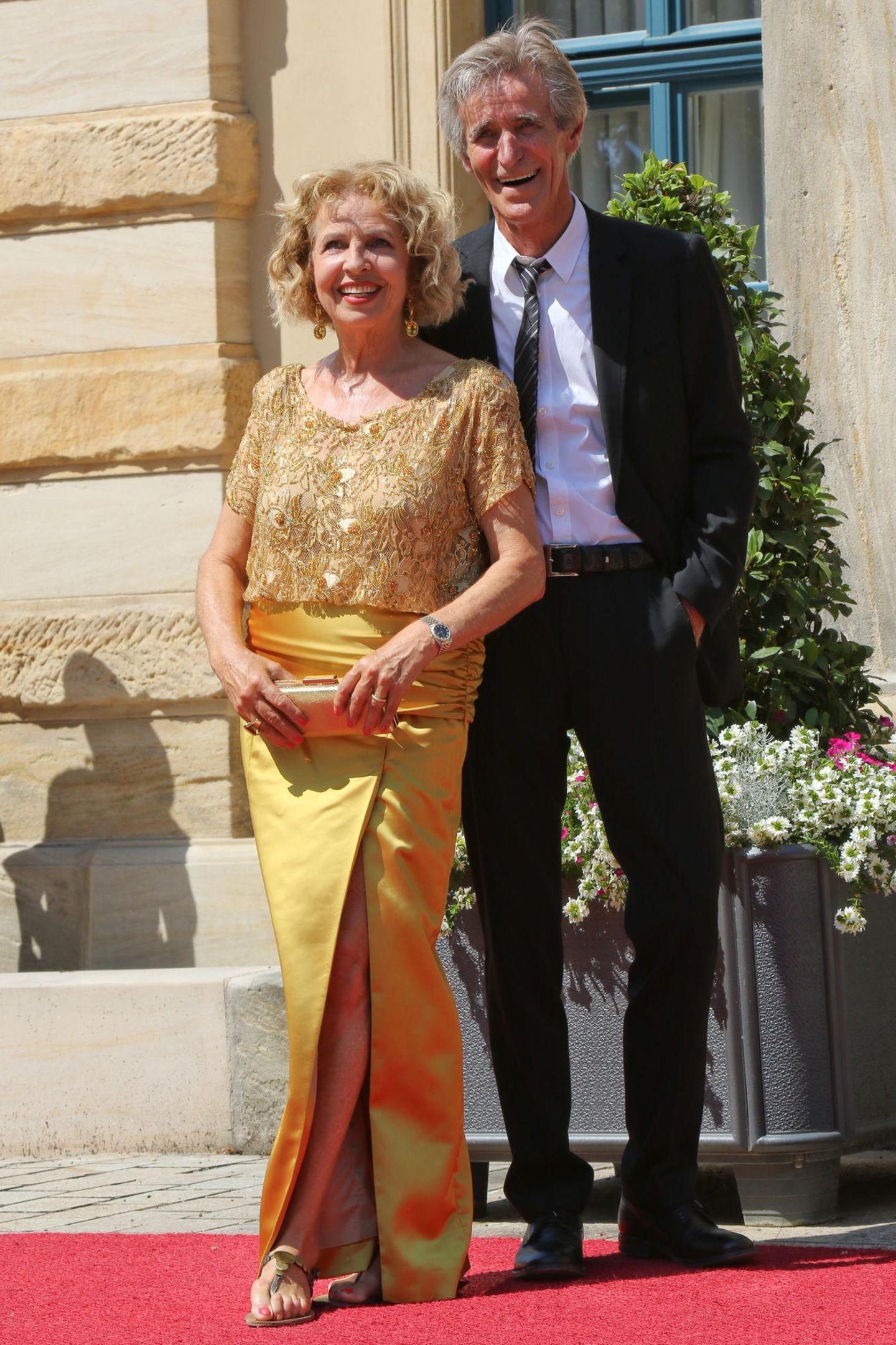 Schauspielerin Michaela May strahlt an diesem Tag mit der Sonne um die Wette. Ihr MannBernd Schadewald ist zwar nicht so schön farbenfroh gekleidet, ist aber dennoch bester Laune.