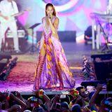 """Wow, was für ein Auftritt. Bei ihrem """"Heimspiel""""-Konzert in Aspach sorgt Andrea Berg mit diesem farbenfrohen Bühnenoutfit für ordentlich Aufsehen. Zu dem Kleid mit hohen Beinschlitzen trägt der Schlagerstar pinkfarbene Overknee-Sandalen."""