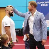 """25. Juli 2019  Bei seinem Besuch der """"Invictus 2020 UK Trials"""" in Sheffield zeigt Prinz Harry keinerlei Berührungsängste und legt bei der Glatze von Jonathan Mitchell Hand an."""