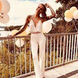 Im weißen Jumpsuit geht Sophia Thomalla zur Sommerparty von Udo Waltz, der seinen 75. Geburtstag feiert. Die lockereWasserfall-Camisole steht dabei im Kontrast zu den geradenHosenbeinen. Der Taillengürtel verbindet beide Formen miteinander.
