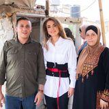 Bei einem Besuch der StadtAl Salt trägt Königin Rania von Jordanien eine weiße Oversize-Bluse von Victoria Beckham, deren Taillenabschnitt schwarz gefärbt ist und durch einen pinken Bindegürtel akzentuiert wird.