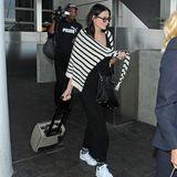 So trägt Demi ein schwarzes Maxi-Kleid und weiße Sneaker während ihres Flugs. Ein gestreifter Strickpullover in Schwarzweiß nimmt die Farbtöne ihres Looks perfekt auf. Eine XL-Sonnenbrille und eine schwarze Crossbag geben ihrem Outfit ein stylishes Update.