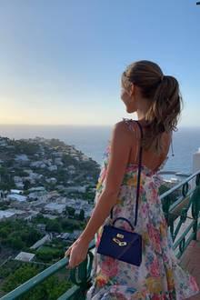 Was für eine Aussicht - und damit meinen wir nicht nur den unvergleichlichen Blick auf Capri! Auch Ann-Kathrin Götzes tolles Outfit bestehend aus einem floralen Sommerkleid von It-Label Zimmermann und einer Miniversion der ikonischen Kelly Bag von Hermès kann sich sehen lassen.