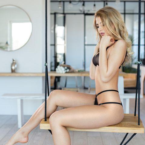 Liebesschaukel, blonde Frau in Unterwäsche auf Liebesschaukel