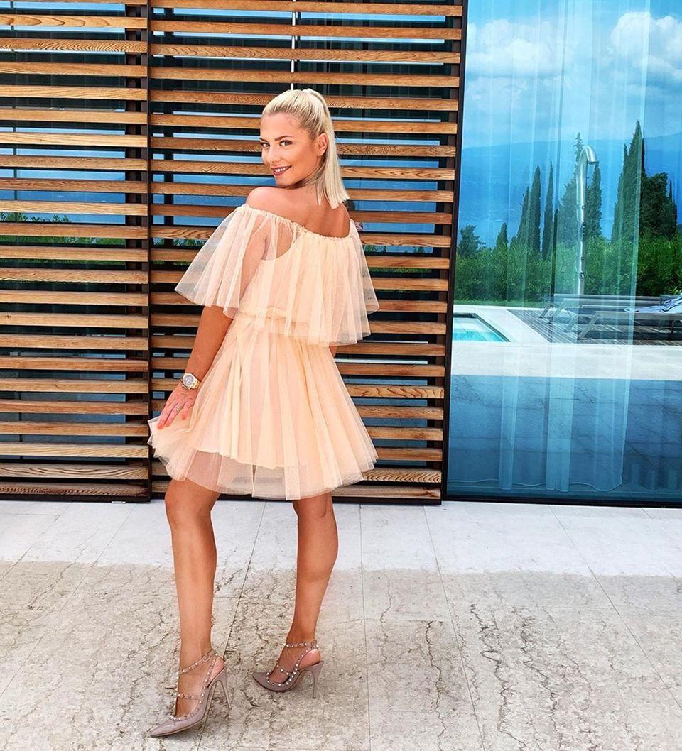 Schauspielerin Valentina Pahde macht als Hochzeitsgast eine prima Figur: Das Off-Shoulder-Kleid des französischen Labels Maje ist durch die zwei ausgestellten Tülllagen verspielt und sexy zugleich. Dazu kombiniert die hübsche Blondine nudefarbene Stilettos mit Nietenapplikationen des Labels Valentino für 720 Euro. Siestylt das 295-Euro-teure Kleid ähnlich wie ...