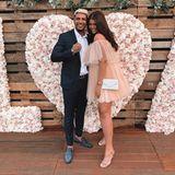 """... Influencerin Farina Opoku. Auch sie trägt das verspielte Maje-Kleid auf einer Hochzeit und setzt beim Styling auf verzierte Nude-Sandaletten und eine goldfarbene Armbanduhr. Die""""Monogram"""" Henkeltasche von Yves Saint Laurent für1190 Euro rundet ihrenLook ab."""