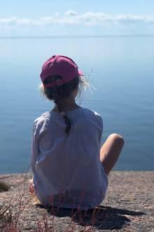 Schwedens Königsfamilie rund um Prinzessin Victoria und Prinz Daniel genießt die traumhafte Landschaft der unbewohnten InselBlå Jungfrun – einem Nationalpark. Mit einemrosafarbenen Käppi auf dem Kopf und auf einer Steinklippe sitzend, genießt Prinzessin Estelle den Ausblick.