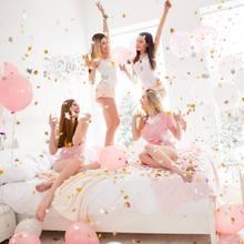 Junggesellinnenabschied, vier junge Frauen auf einem Bett, rosafarbene Luftballons, Konfetti, Sekt