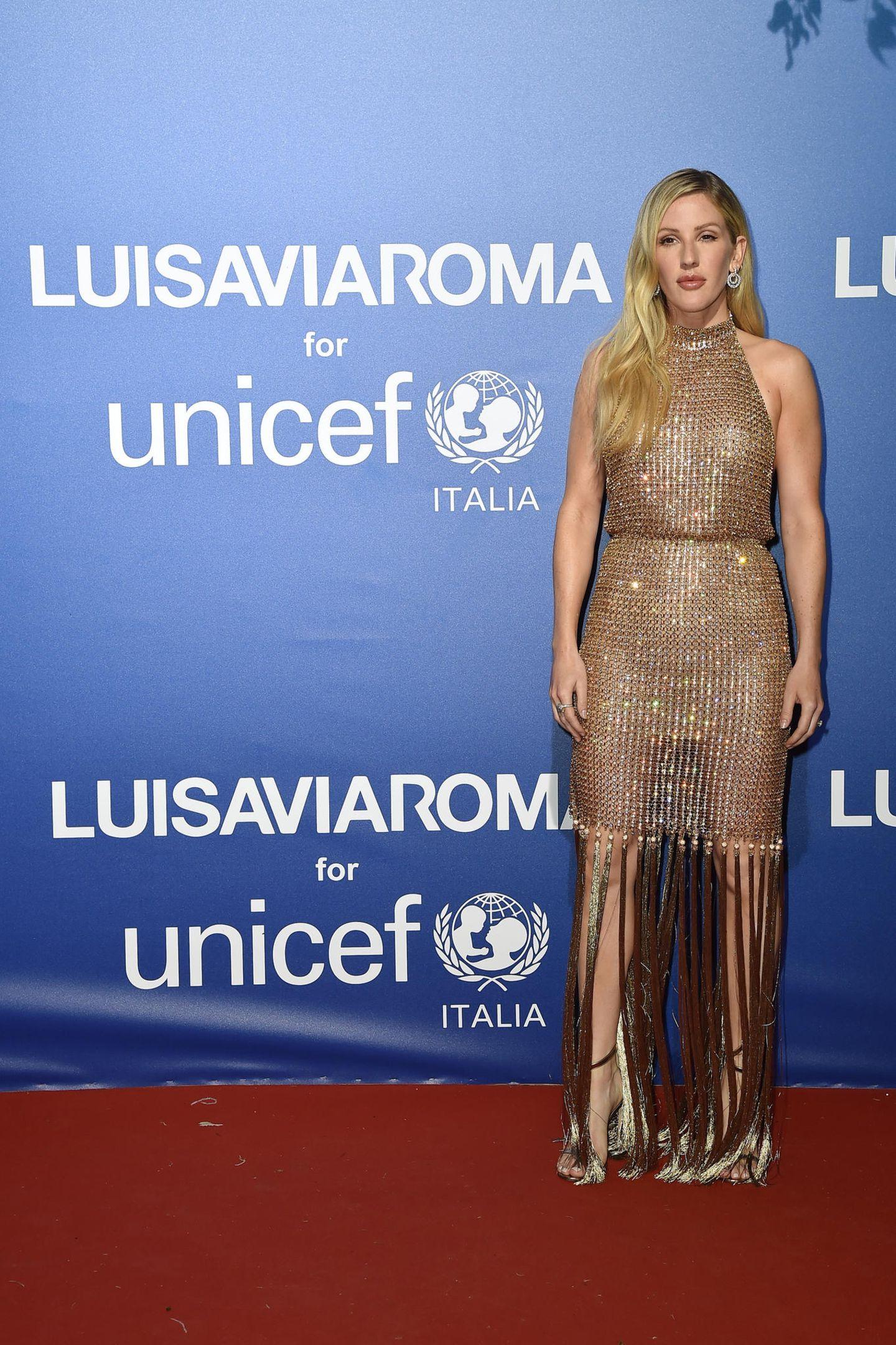 Ellie Goulding setzt ebenfalls auf Glitzer. Das Kleid hat Fransendetails am Rock und ist tailliert. Dazu trägt sie die Haare offen und Make-up in Brauntönen.