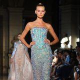 Auch das Model auf dem Runway der Haute-Couture-Show von Rami Kadi setzt die Glitzerrobe toll in Szene. Ein tougher Ausdruck und die streng zurückgekämmten Haare runden den Look ab.