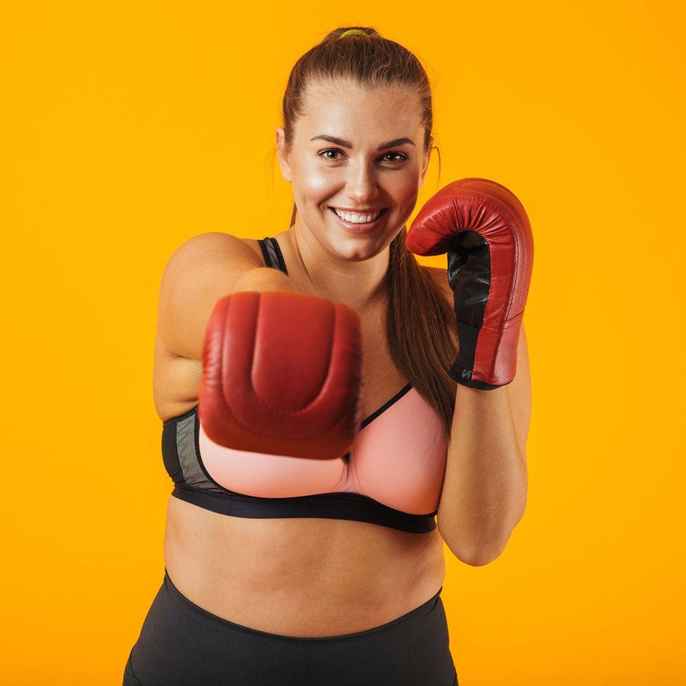 Sport-BH große Größen, junge Frau im Sport-BH trägt Boxhandschuhe