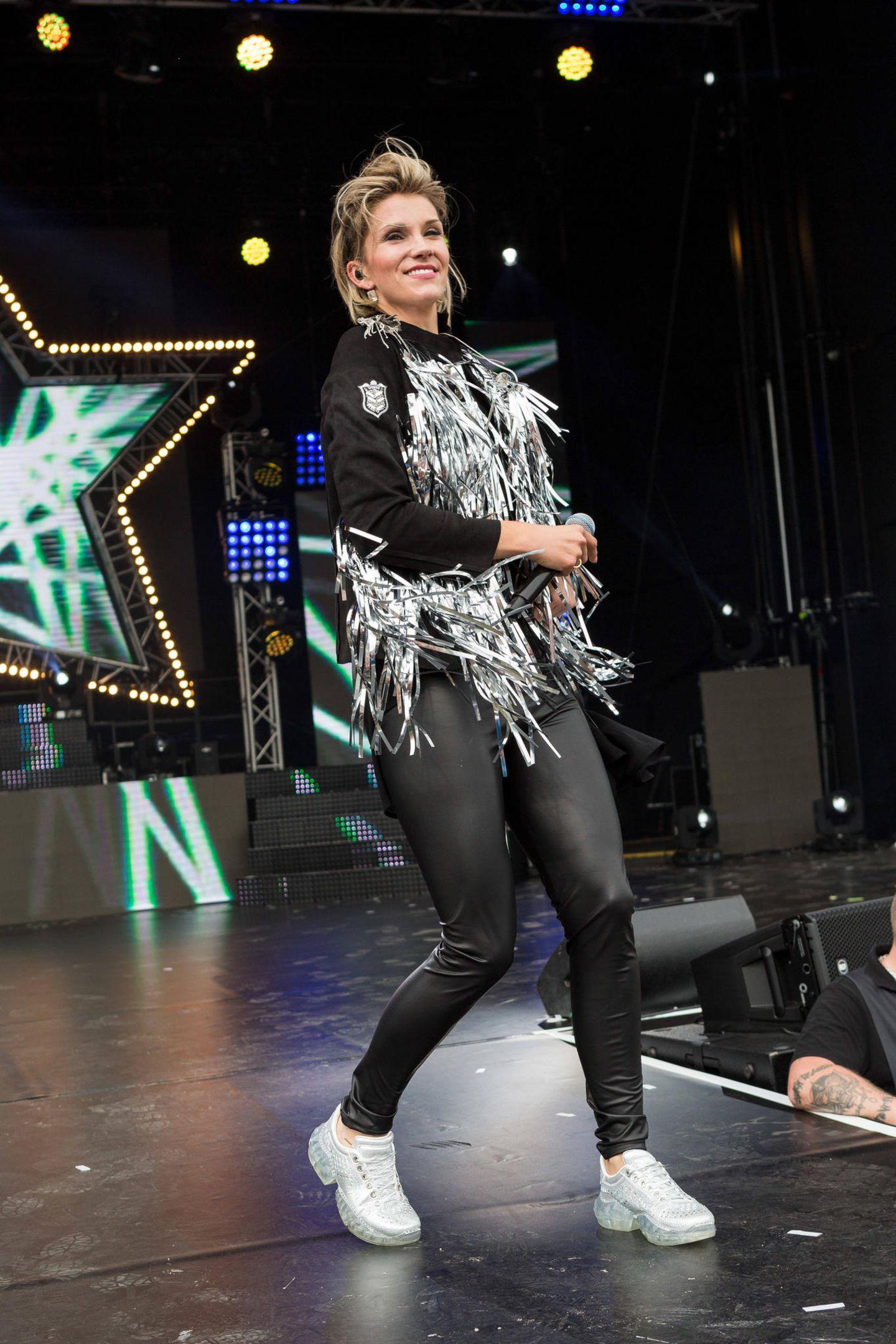 Auch Anna-Maria Zimmermann rockt beim Sauerland Open Air Festival in einer Leggings in Lederoptik und einem Parker mit auffälligen Metallic-Fransen die Bühne. Weiße Sneaker runden den sportlichen Look der Sängerin gekonnt ab.