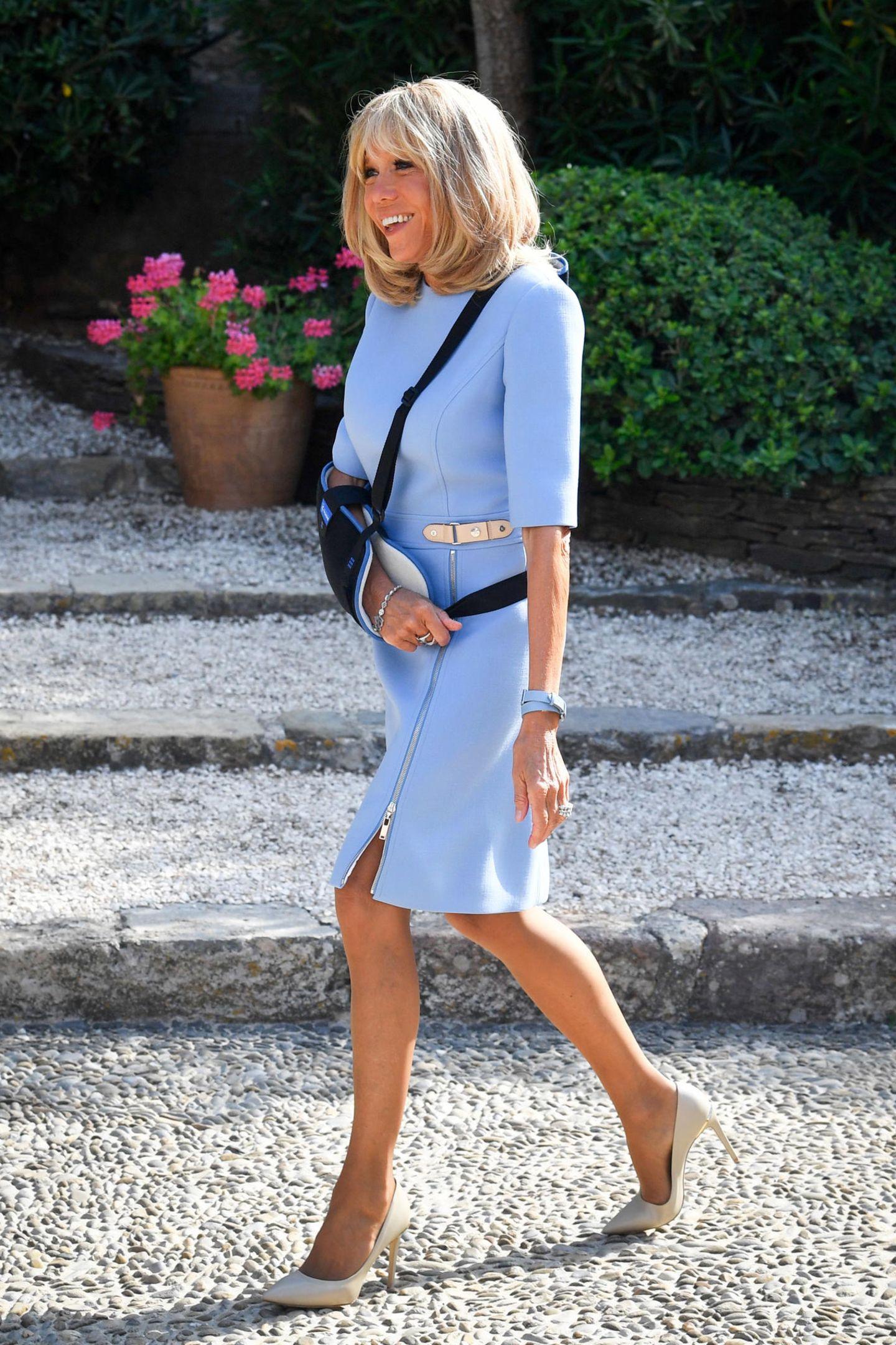 First Lady Brigitte Macron trägt ein hellblaues Kleid mit raffinierten Details von Louis Vuitton. Ein seitlicher, deutlich sichtbarer Reißverschluss lässt sich bis zurTaille öffnen, dortbefinden sich Schnallen aus beigefarbenem Leder. Farblich passend wählt Brigitte beigefarbene Pumps zu diesem sommerlichen Look. Ihren Arm trägt die 66-Jährige in einer Schlinge - sie soll Medienberichten zufolge auf einem Boot gestürzt sein.