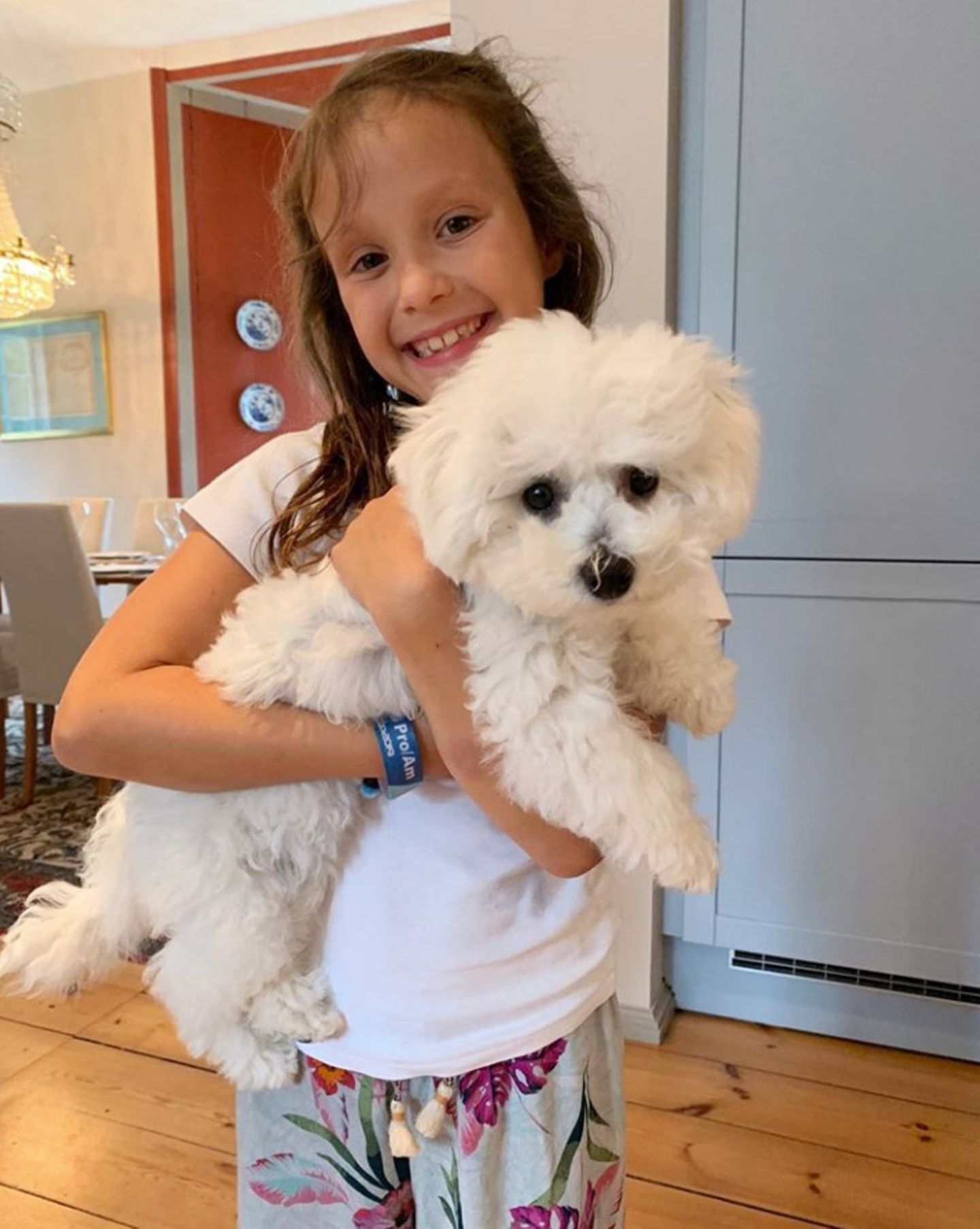 """21. August 2019  Stolz präsentiert Prinzessin Athena das neue, kuschelige Familienmitglied:Der kleine Hund ist eine Bichon Frisé namens Cerise, was übersetzt """"Kirsche"""" bedeutet. Damit bleiben Prinzessin Marieund Prinz Joachim ihrer Tradition treu, denn ihr verstorbener Hund hieß bereits """"Apple""""."""