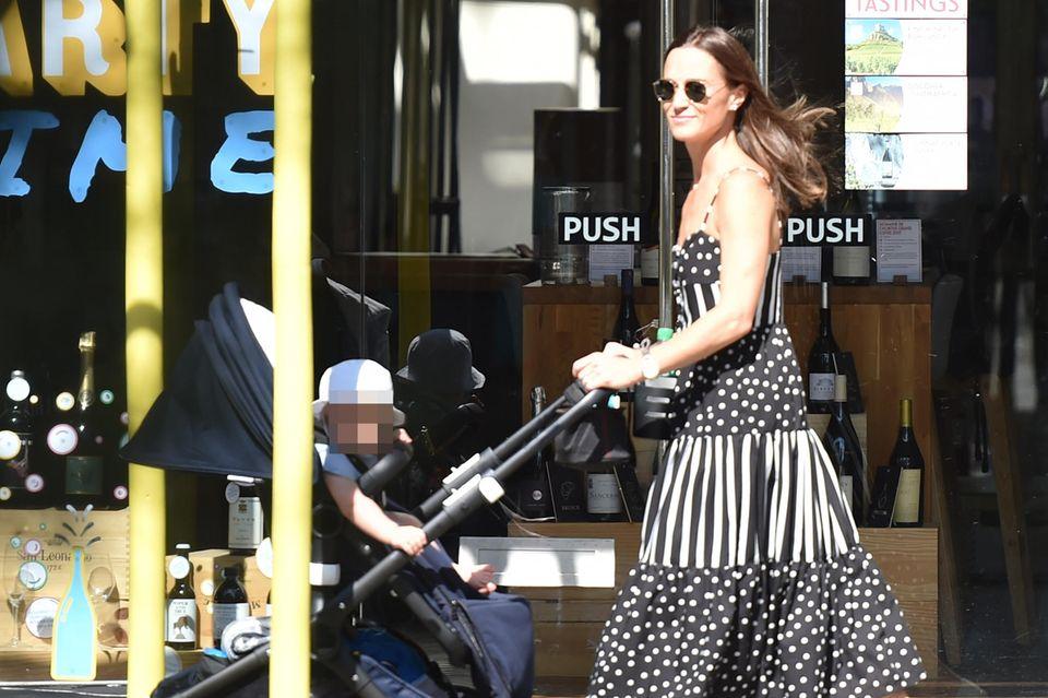 """Pippa Middleton läuft strahlend durch die Straßen des Londoner Nobelviertels Chelsea. Söhnchen Arthur sitzt mit einem niedlichen Sonnenhut im Kinderwagen. Zu ihrem gestreift-gepunkteten Kleid von """"Solid & Striped"""" für rund 285 Euro kombiniert sie weiße Sneaker. Während sie die sommerlichen Temperaturen in London genießt, wurden ihre Eltern zusammen mit den Cambridges auf dem Weg nach Schottland gesichtet - sie besuchen dort die Queen in ihrer Sommerresidenz."""
