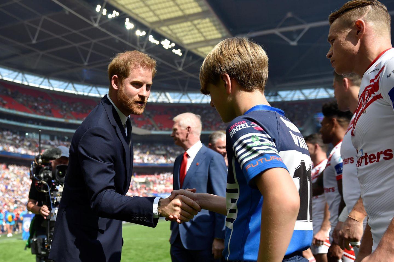 24. August 2019  Prinz Harry schüttelt vor vielen tausend Zuschauern die Hände der Ballkinder beim Finalspiel desRugby League Challenge Cup im Londoner Wembley Stadium. Schade nur, dass er Meghan nicht mitgenommen hat.