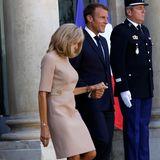 In einem engen, beigen Kleid von Louis Vuitton erscheint Brigitte Macron an der Seite ihres Mannes für ein Treffen mit dem griechischen PremierministerKyriakos Mitsotakis. Dazu kombiniert sie braune Wildlederpumps.