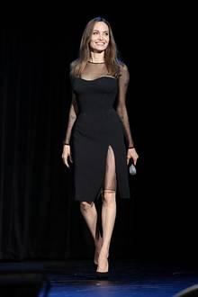 Während einer Disney-Präsentation zeigt sich Angelina Jolie strahlend schön und ganz in Schwarz. Das enge, knielange Kleid von Versace besticht durch einen hohen Beinschlitz und durchsichtige Einsätze, die die tolle Figur der Schauspielerin perfekt in Szene setzen.