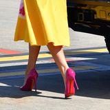 Dazu kombiniert sie knallig pinke, schwindelerregend hohe Heels von Louboutin, die perfekt zum Print ihres Kleides passen.