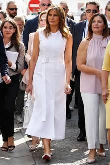 In den Straßen von Espelette zeigt sich Melania Trump ganz in Weiß. Sie trägt ein sommerliches Kleid und hält eine farblich passende Handtasche von Hermès. Ein Gürtel mit filigraner Silberschnalle betont ihre schmale Taille.
