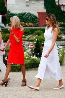 Melania trägt als Einzige flache Schuhe - wie so oft von Louboutin. Die spitzen, weißen Ballerinas passen perfekt zu ihrem weißen Kleid mit Beinschlitz.