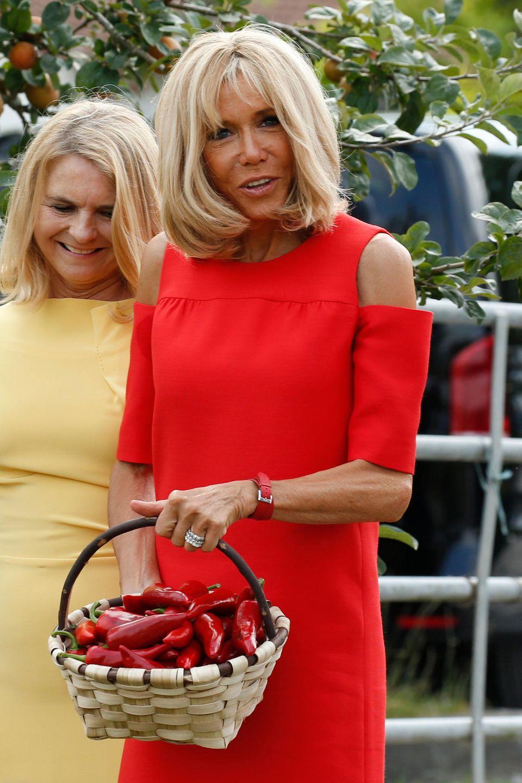 Am zweiten Tag des G7-Gipfeltreffens setzt die 66-Jährige auf eine Knallfarbe: Das gerade geschnittene Kleid mit Cut-Outs an den Schultern stammt, wie ihre Looks des vorherigen Tages, von dem französischen DesignerlabelLouis Vuitton. Als hätte Brigitte Macron es geplant: IhrHingucker-Dresspasst perfekt zu den Chili-Schoten in ihrem Korb.