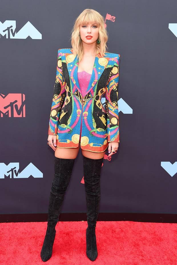 Taylor Swift zeigt sich sexy in Korsage, Jackett und Overknee-Stiefeln. Das Augen-Make up ist ganz dezent, dafür stechen die knallroten Lippen hervor.