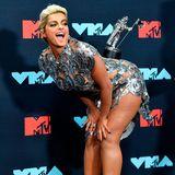 """Bebe Rexha balanciert ihren Award für das """"Beste Dance-Video"""" für die Fotografen auf dem Rücken."""