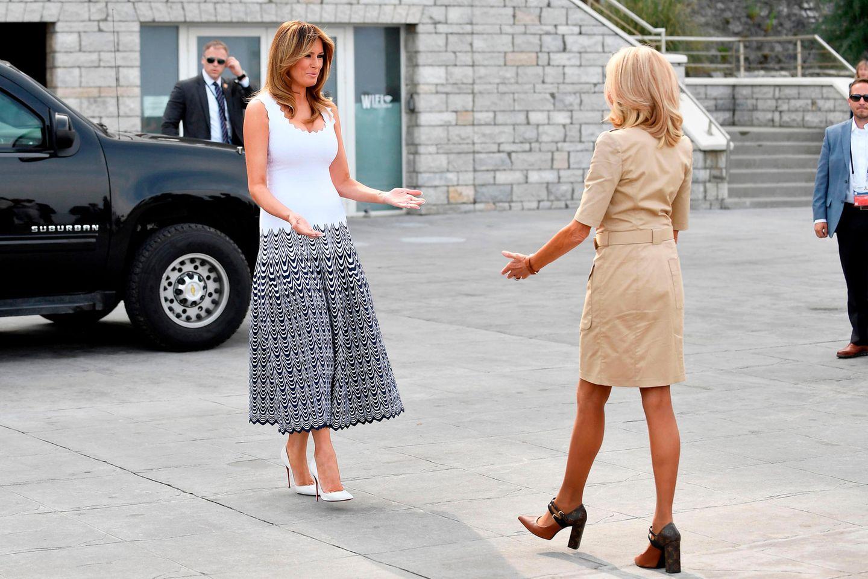 Melania Trump trägt ein Midi-Kleid des Labels Alaïa (ca. 3.120 Euro), das bis zur Hüfte aus einem weißen Top besteht und dann in einen grafischen Rock übergeht. Dazu kombiniert die First Lady weiße Pumps von Louboutin.