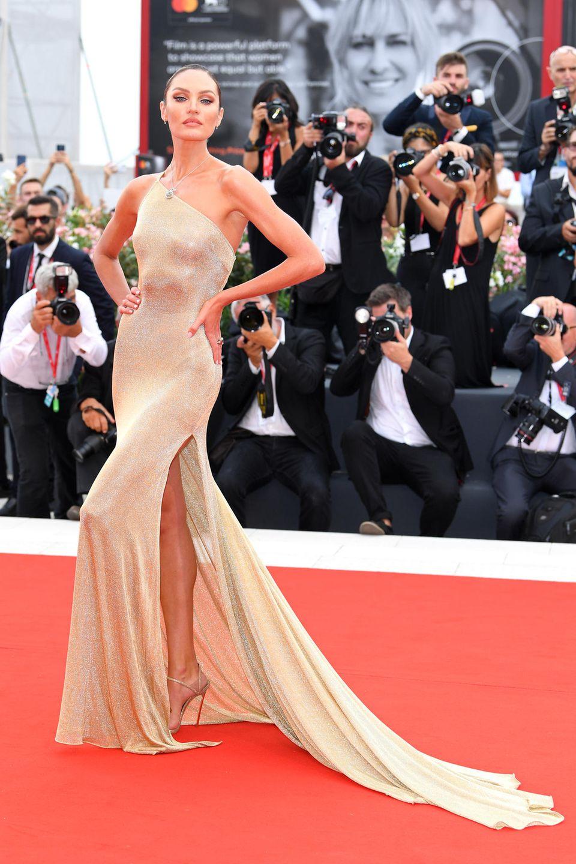 Topmodel Candice Swanepoel posiert anmutig in einer hautengen Robe mit Beinschlitz und One-Shoulder-Schnitt auf dem roten Teppich in Venedig. Das Kleid ist eine Kreation des Labels Etro.
