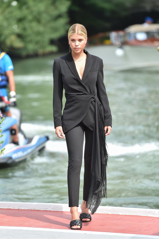 In einer sexy Kombination aus einem Blazer mit Binde-Applikation sowie einer engen schwarzen Jeans steigtSofiaRichie aus der Gondel in Venedig.