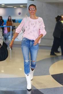 """Hey Cowgirl! In weißen Cowboy-Boots stapft Heidi Klum überden Flughafen von Los Angeles. Ein rosafarbener Strickpullover und eine hellblaueJeans runden ihren farbenfrohen Airport-Style ab und beweisen, dass die 46-Jährige """"Reiseprobleme"""" wie jeder andere auch hat. Denn: DerobersteKnopf ihrer Jeans ist immer noch geöffnet, als Paparazzi Heidi auf dem Weg zum Taxi erwischen. Lange Reisen in Skinny Jeans sind eventuell nicht die bequemste Kleiderwahl und können am Bauch ganz schön kneifen."""