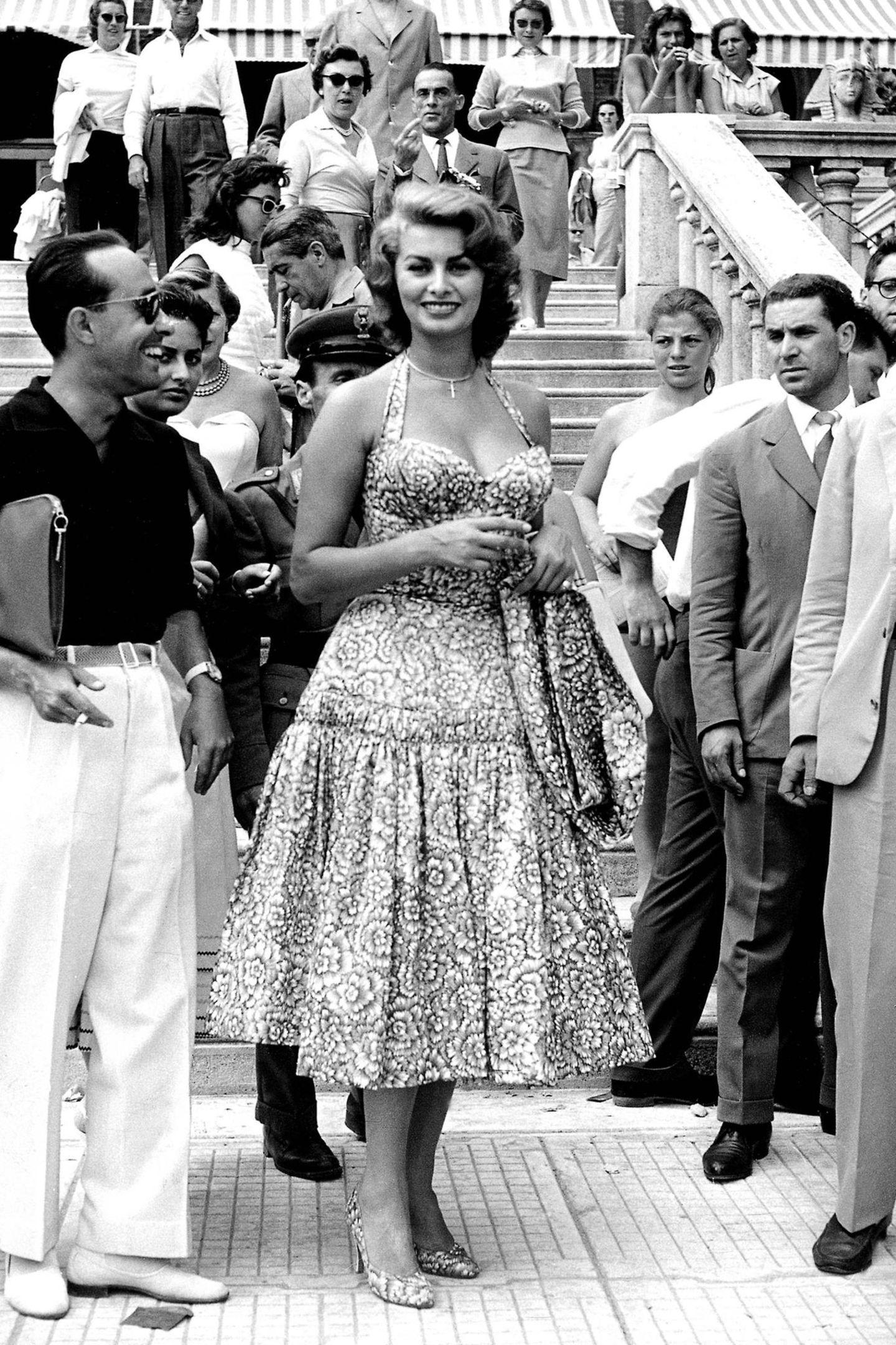 Filmikone Sophia Loren weiß bereits in 1955, dass ein All-Over-Print absolut modisch ist. Bei ihr passen Kleid, Pumps und Jäckchen perfekt zusammen.