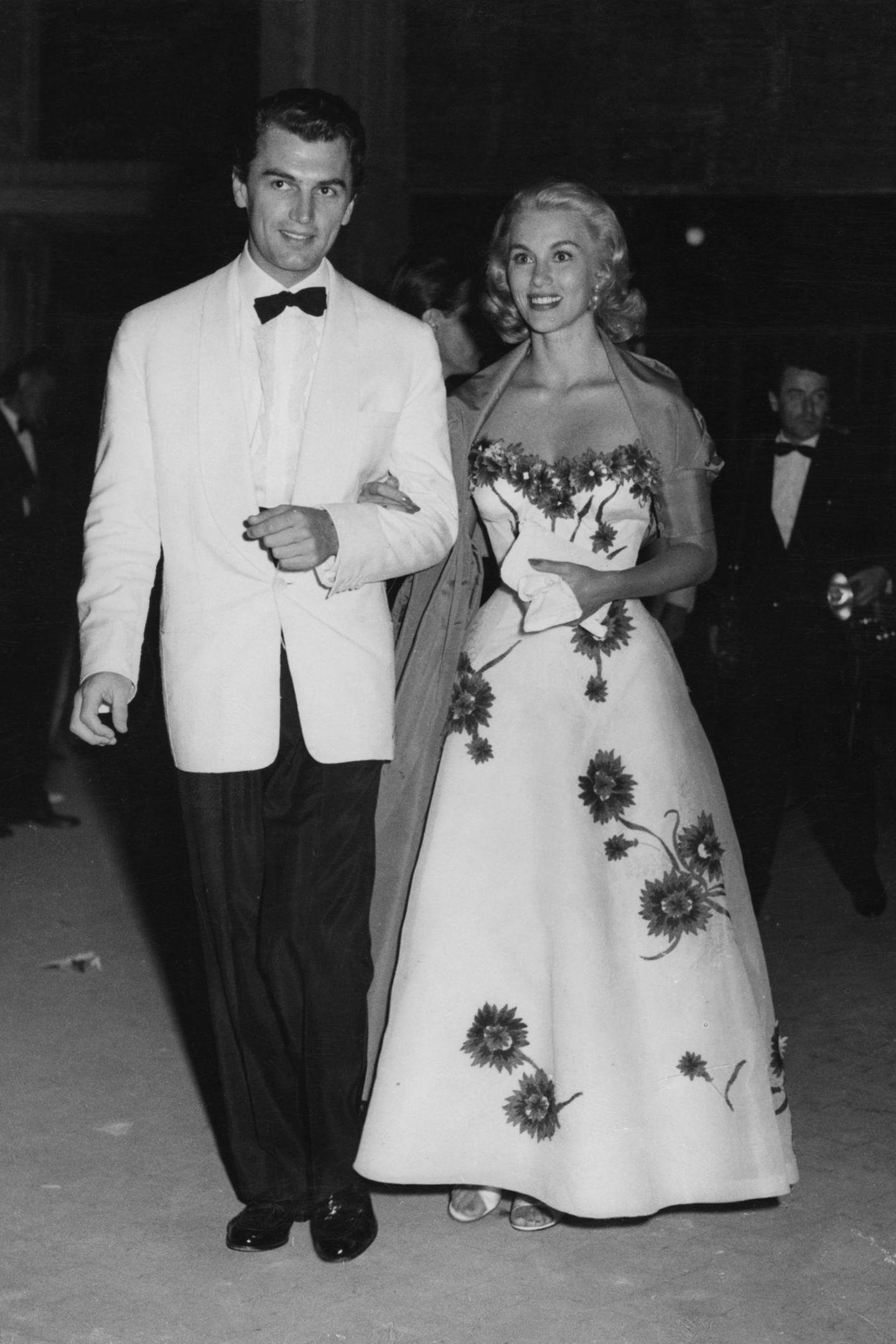 Bondgirl Lina Christian ist 1955 der absolute Hingucker beim Filmfest. Ihr Kleid betont ihre Taille ganz wundervoll, der Ausschnitt wirkt durch die Blumenapplikationen besonders.