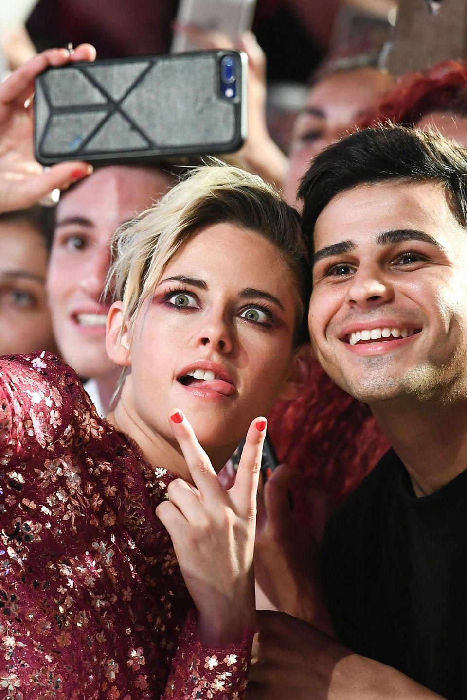"""Für ein Selfie mit diesem Fan, schneidet Schauspielerin Kristen Stewart bei ihrer Ankunft zur Filmvorführung von """"Seberg"""" lustige Grimassen."""