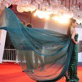 """Model Peechaya Wattanamontree hat zur """"""""J'Accuse""""-Premiere extra einen Helfer mitgebracht, der ihr auf dem roten Teppich die imposante Schleppe ihres Kleides drapiert."""