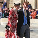 Der britische Sänger James Blunt erscheint gemeinsam mit seiner EhefrauSofia Wellesley. Diese trägt ein rotes Blumenkleid und kombiniert es - wie die Etikette es verlangt - mit einem Hut.