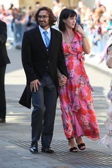 Fitnessguru Joe Wicks kommt in Begleitung seiner Frau Rosie, die sich für ein besonders farbenfrohes Dress in Pink und Rot entschieden hat.