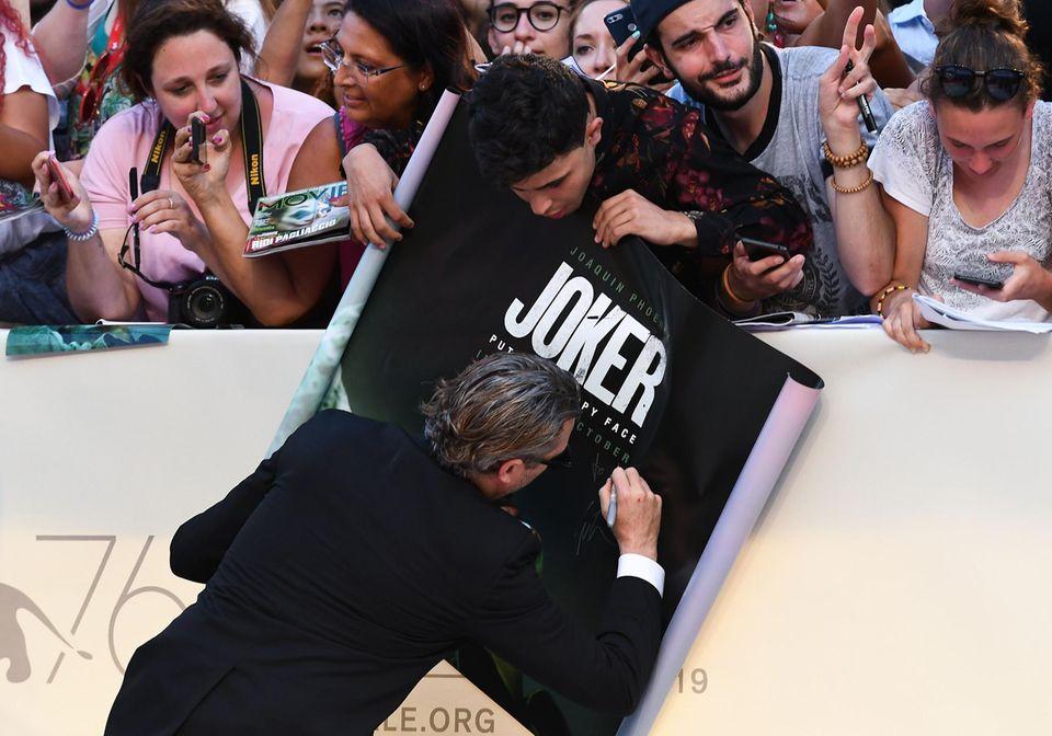 """""""Joker""""-Darsteller Joaquin Phoenix ist nämlich gerade noch dabei Fans ihre Autogrammwünsche zu erfüllen."""