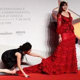 Um ihr Kleid in voller Pracht präsentieren zu können, bekommt Monica Bellucci ein wenig Hilfe von einer Assistentin.