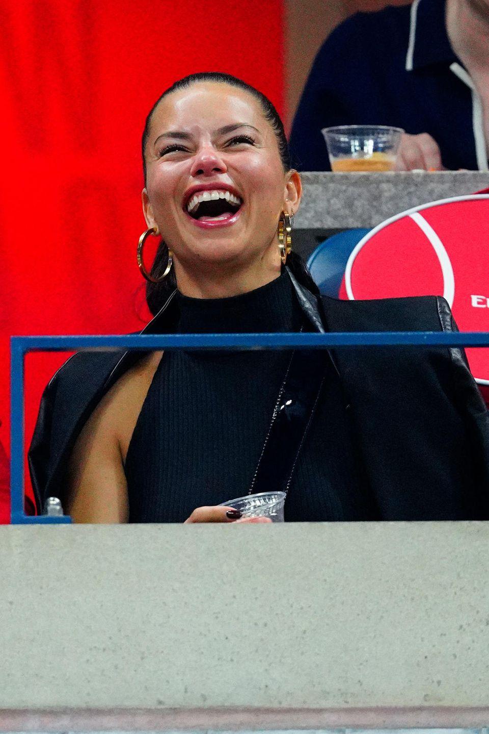 Doch nicht nur beim Posing vor der US-Open-Fotowand, sondern auch auf demZuschauerrangmacht Adriana Lima herzlich lachend eine gute Figur.