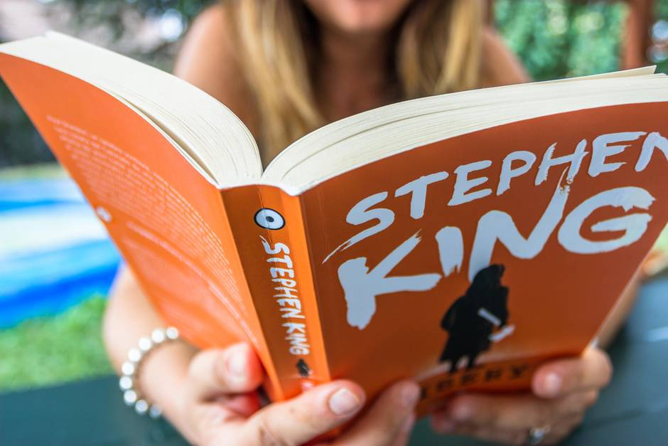 """Stephen-King-Buch, Frau liest in dem Buch """"Misery"""" von Stephen King"""