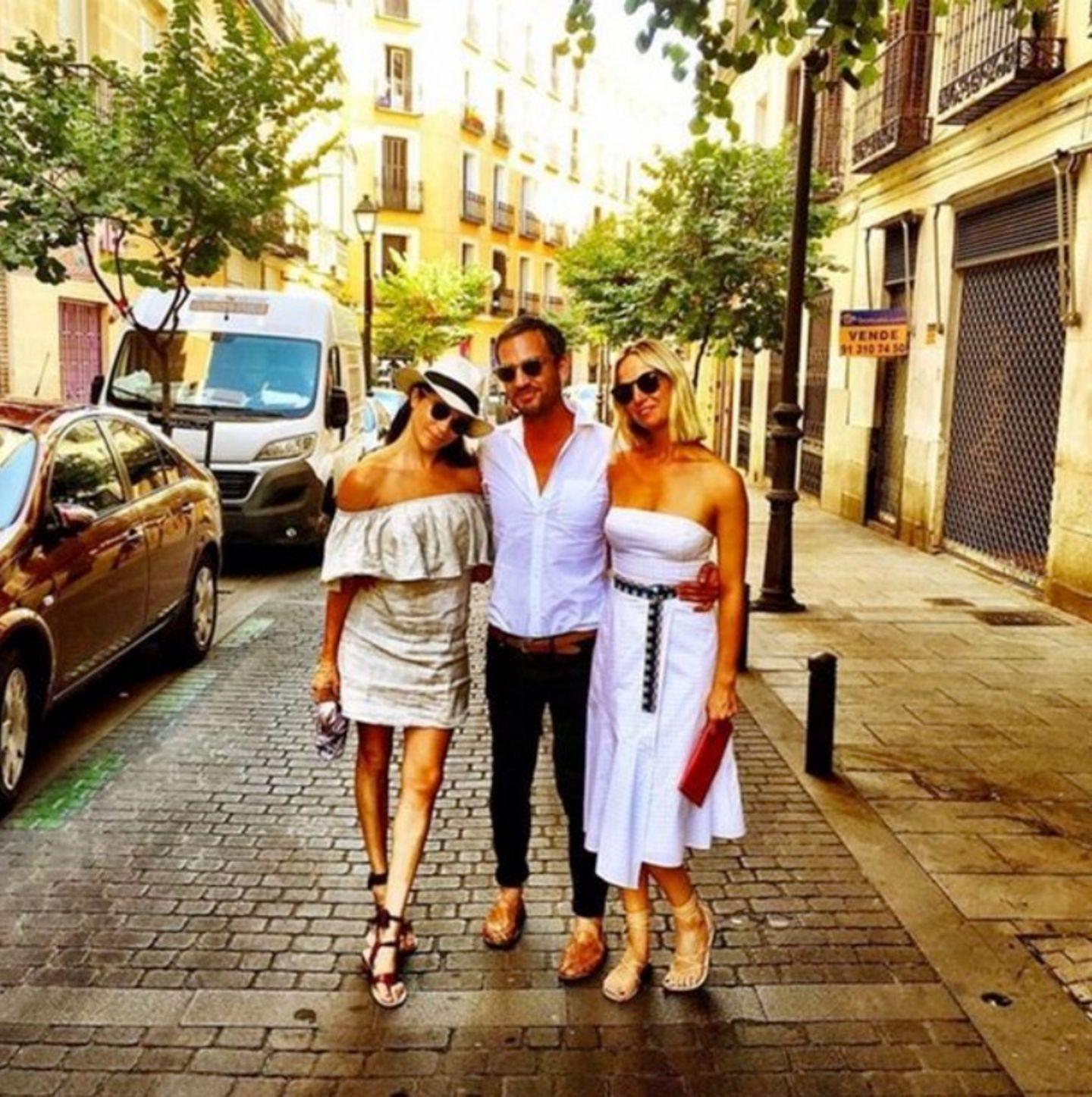 Auf den Straßen Madrids schlendert Meghan mit zwei Freunden in einem schulterfreien Mini-Kleid undihrem Lieblingsaccessoire für den Sommer: dem Strohhut.