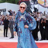 Meryl Streep gibt ihrem blau-glitzernden Look mit einer großen Sonnenbrille das gewisse Etwas. Dazu trägt sie knallrote Pumps und ein strahlendes Lächeln.