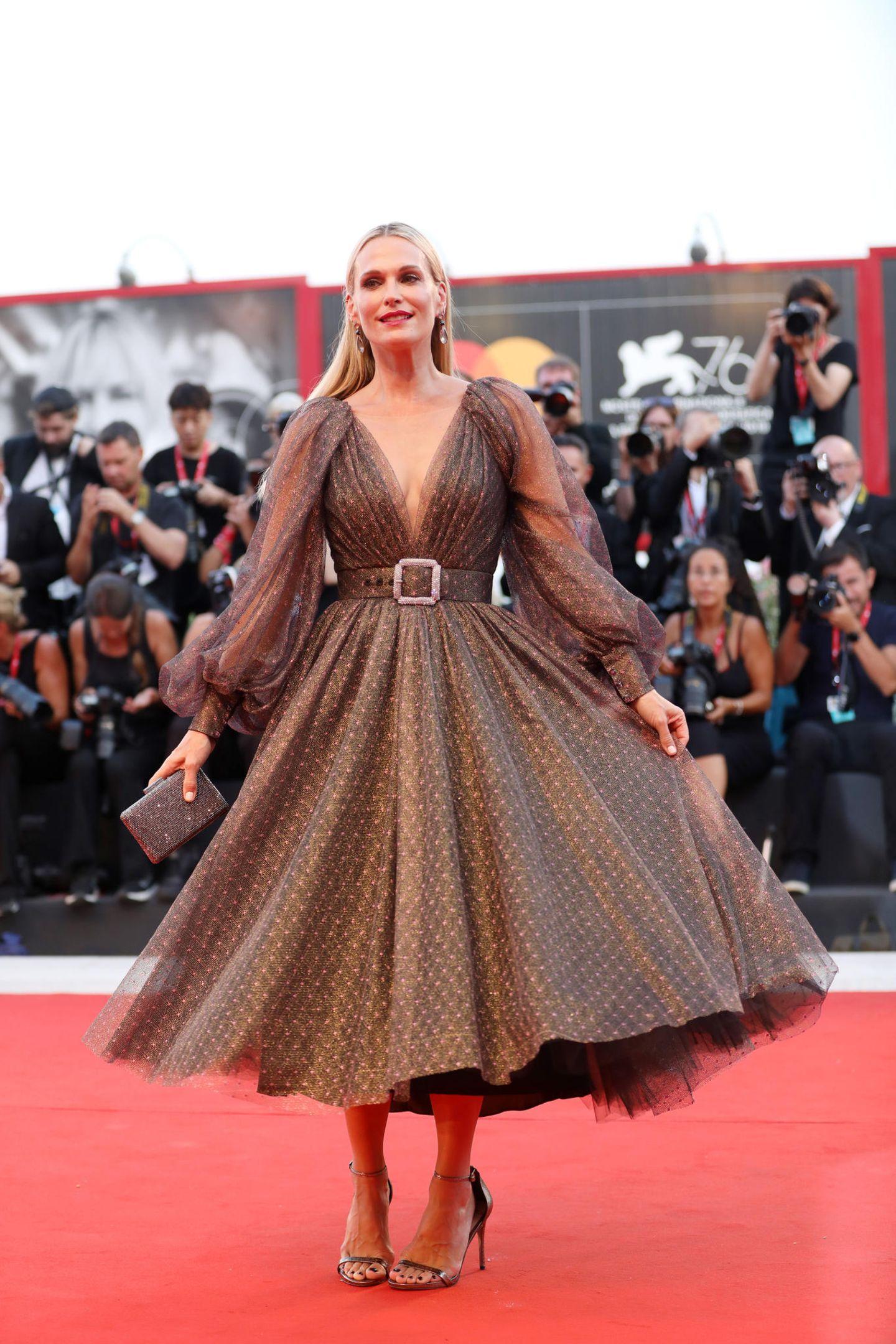 Molly Sims erlebt in ihrem ausgestellten Kleid den großen Auftritt. Zu dem tiefen Ausschnitt, dem Taillengürtel mit Glitzerschnalle und dem opulenten Rock trägt sie natürliches Make-up und offene Haare.