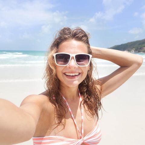 Junge Frau macht Selfie am Strand