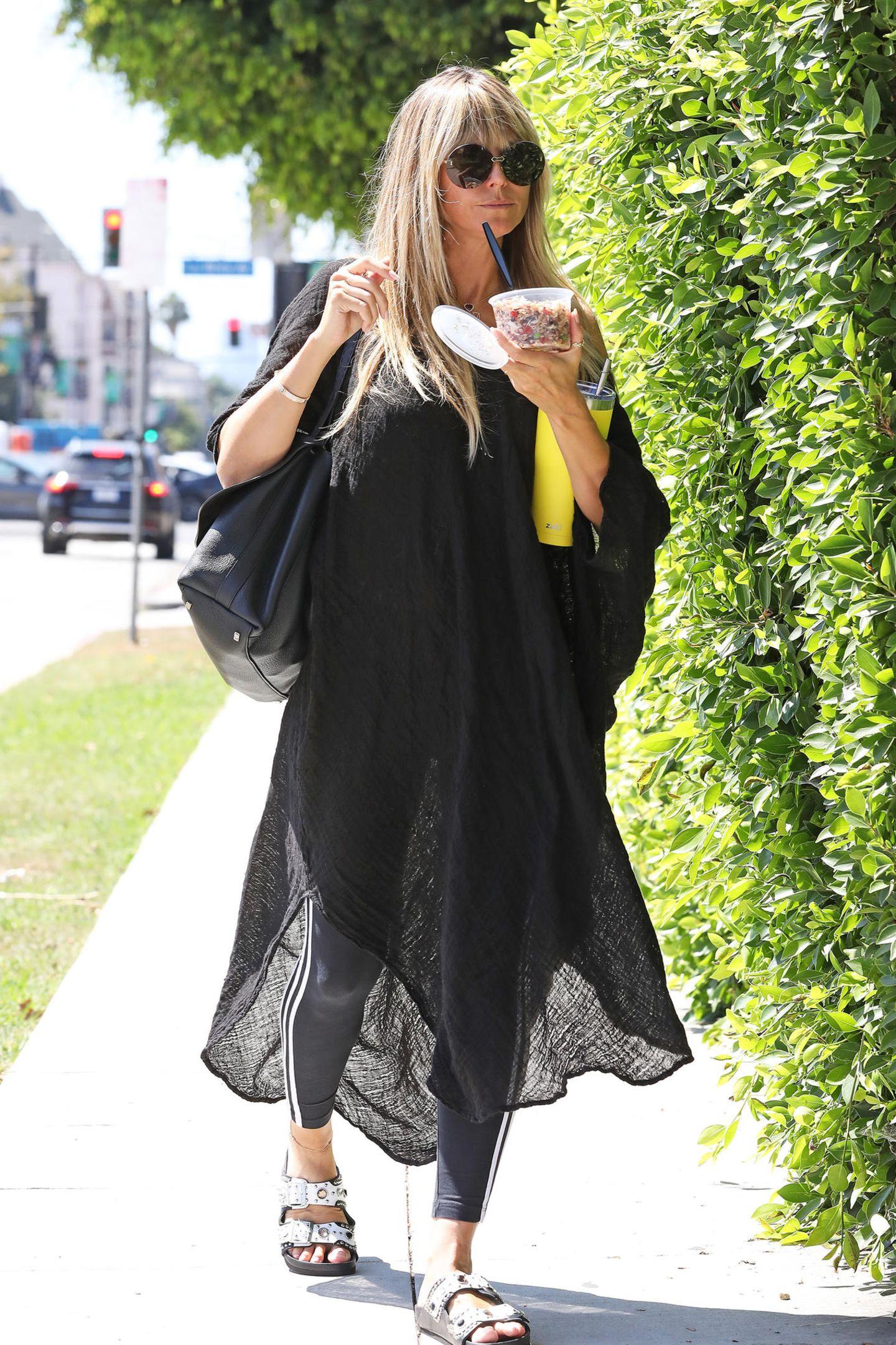 Es sieht nicht nur lässig aus, wie Heidi Klum ihren Couscous-Salat to go isst,auch ihr Outfit versprühteine passende Coolness-Attitude. DenschwarzenKaftan hat das 46-Jährige Topmodel über ihr Sport-Outfit geworfen. BequemeSandalen mit Nieten-Applikationen runden ihren Wohlfühl-Look ab.